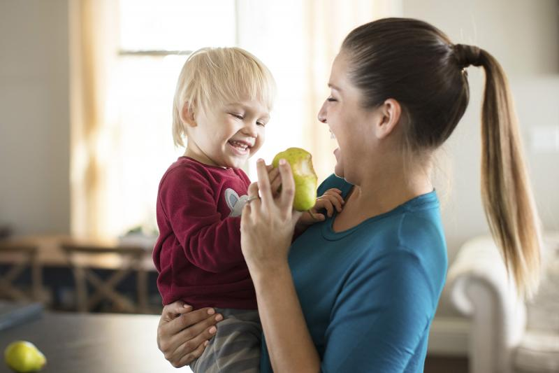 A Caucasian mom feeds her son a pear in the kitchen.