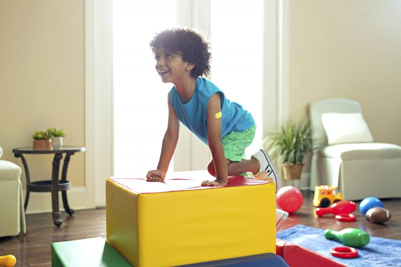 A young African American boy plays on cushioned toy blocks at home.