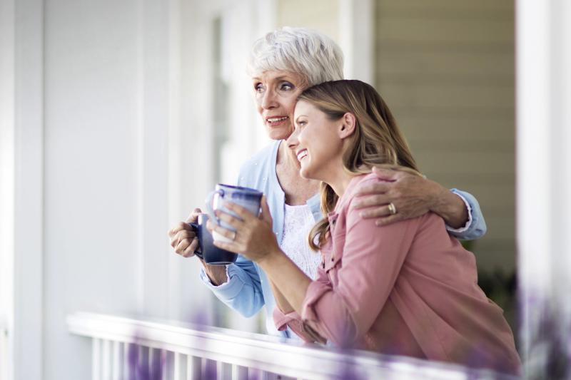 Two women converse on the front porch while drinking coffee.