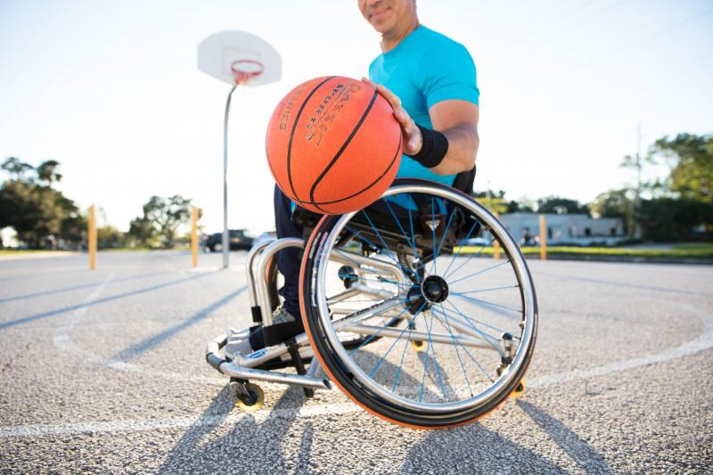 Man playing basketball in a wheelchair.