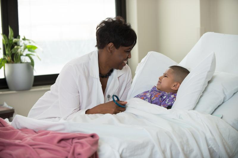 A physician speaks kindly to her young child patient.