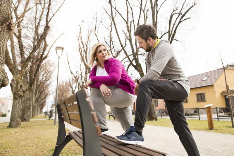 Woman and Man Stretching at Bench