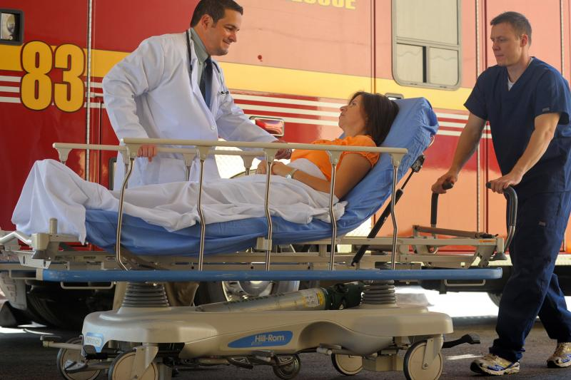 Woman arriving in a stretcher from ambulance with a doctor by her side.