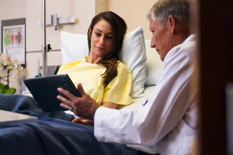 A male doctor goes over a female patient's results on a tablet in her hospital room.