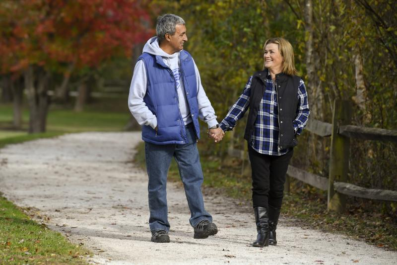 Couple walking down a path outdoors in the fall holding hands.