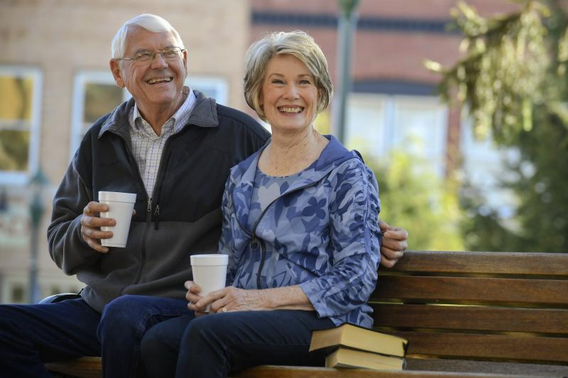 Elderly couple sitting on a park bench drinking coffee.