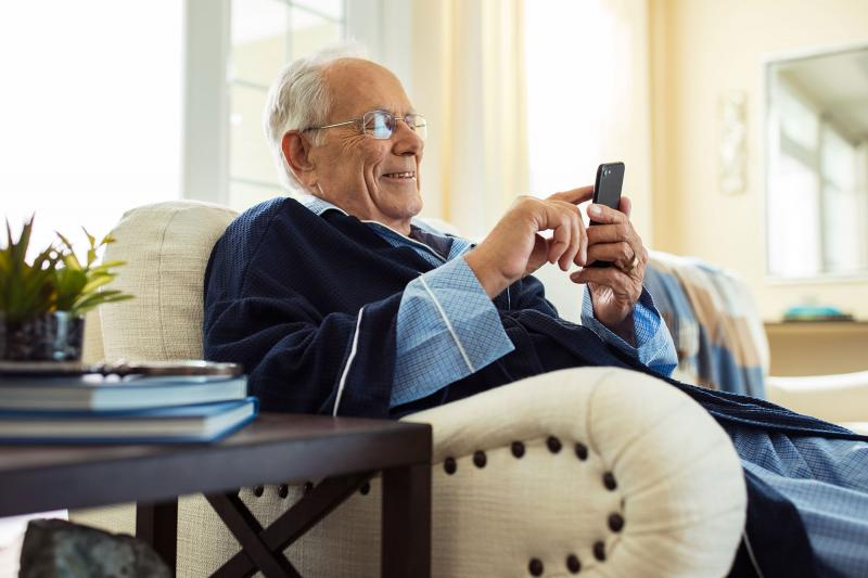 An elderly man relaxing at home seating on his couch.