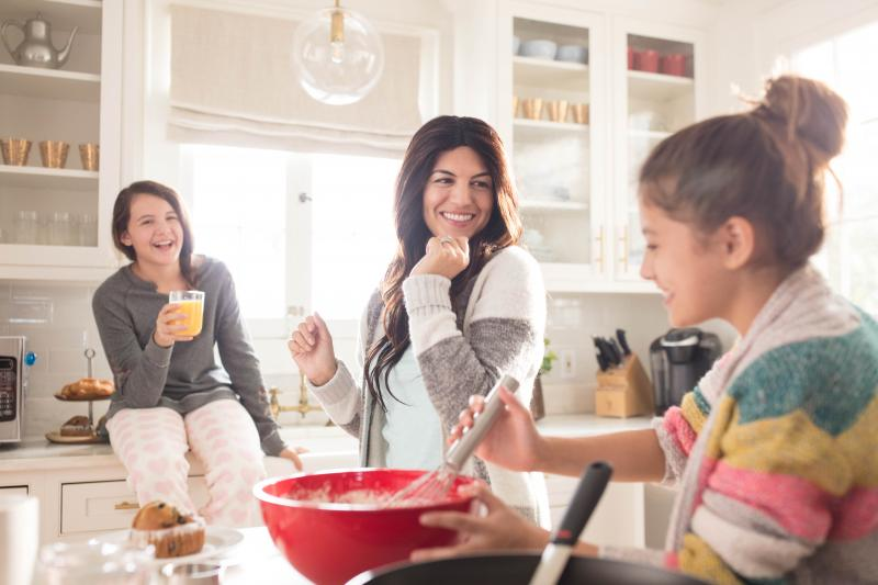 Mother baking with her daughters in the kitchen.