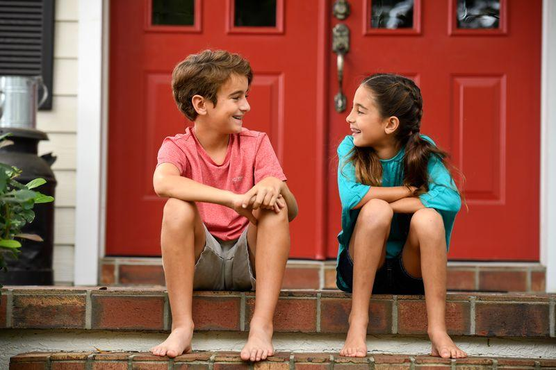A boy and girl make jokes while sitting on their porch