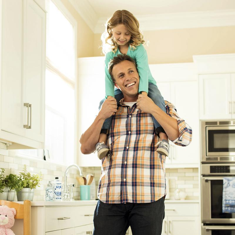 A Caucasian father carries his young daughter on his shoulders in their home.