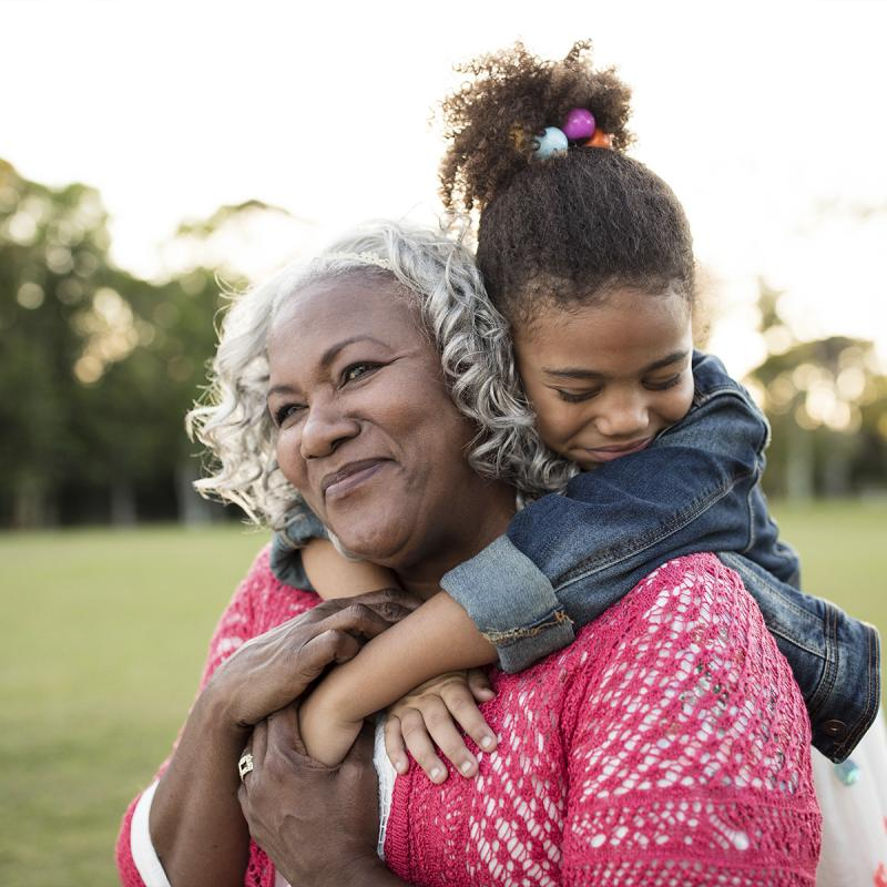 An African American granddaughter embraces her grandmother around the neck.