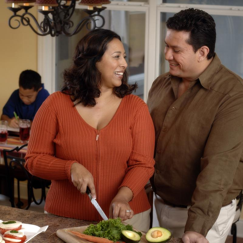 A Hispanic couple prepares a healthy meal for their family in the kitchen.
