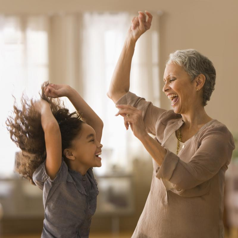 An elementary-aged girl and an older female relative dancing and smiling indoors
