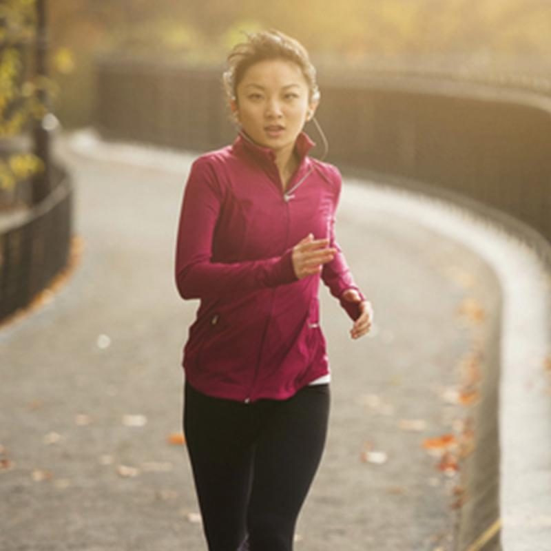 A young Asian woman jogs in the park on a fall afternoon.