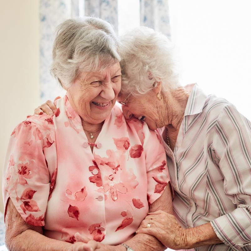 Two older women laugh together while sitting on a bed.