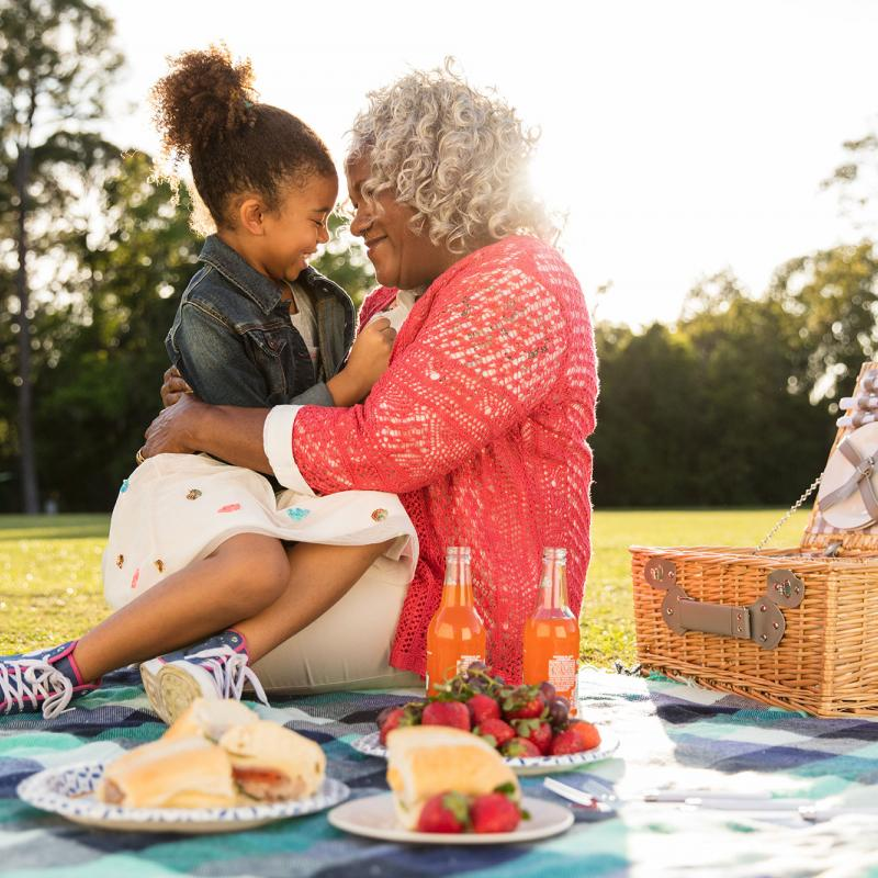 A grandmother having a picnic with her grand-daughter at the park.