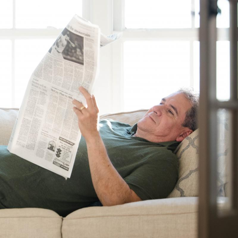 Grandpa is reading the newspaper.