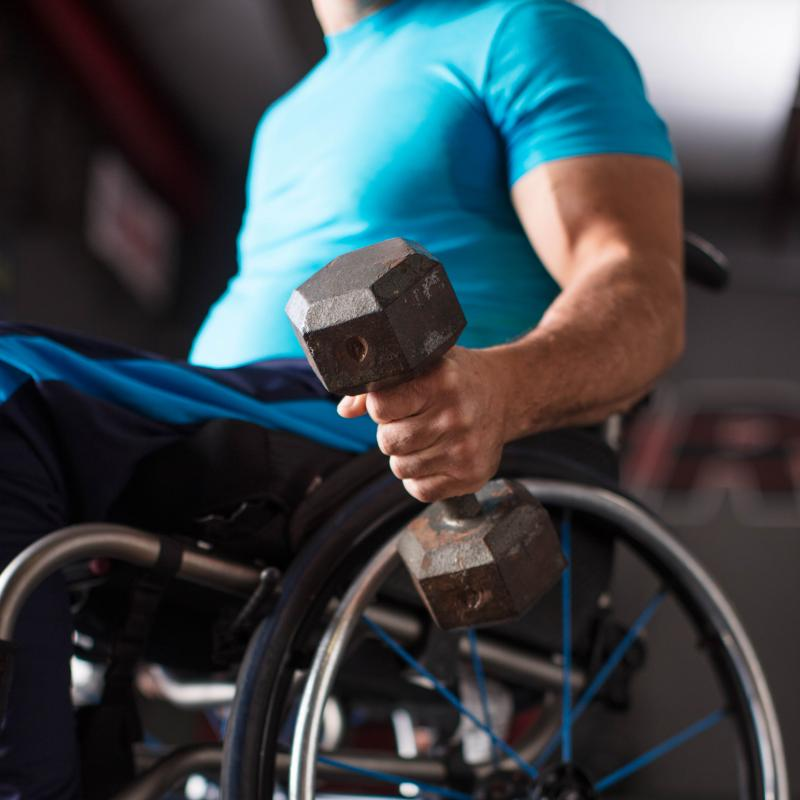 Man in a wheelchair lifting weights.