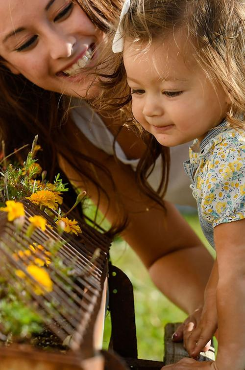 Mother and daughter smelling flowers.