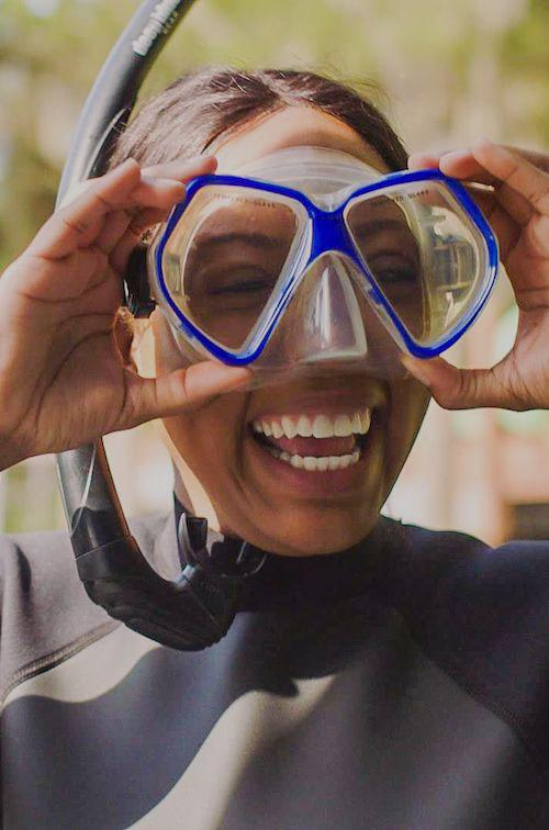 Woman smiling while wearing scuba gear